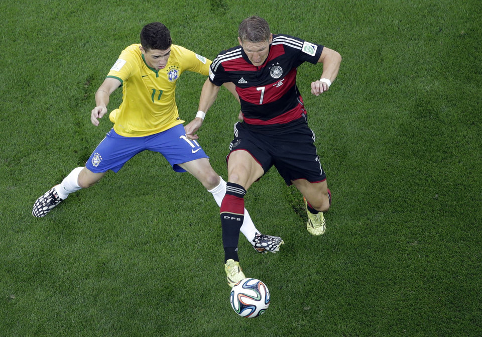 Photo - Brazil's Oscar, left, and Germany's Bastian Schweinsteiger vie for the ball during the World Cup semifinal soccer match between Brazil and Germany at the Mineirao Stadium in Belo Horizonte, Brazil, Tuesday, July 8, 2014. (AP Photo/Felipe Dana, Pool)