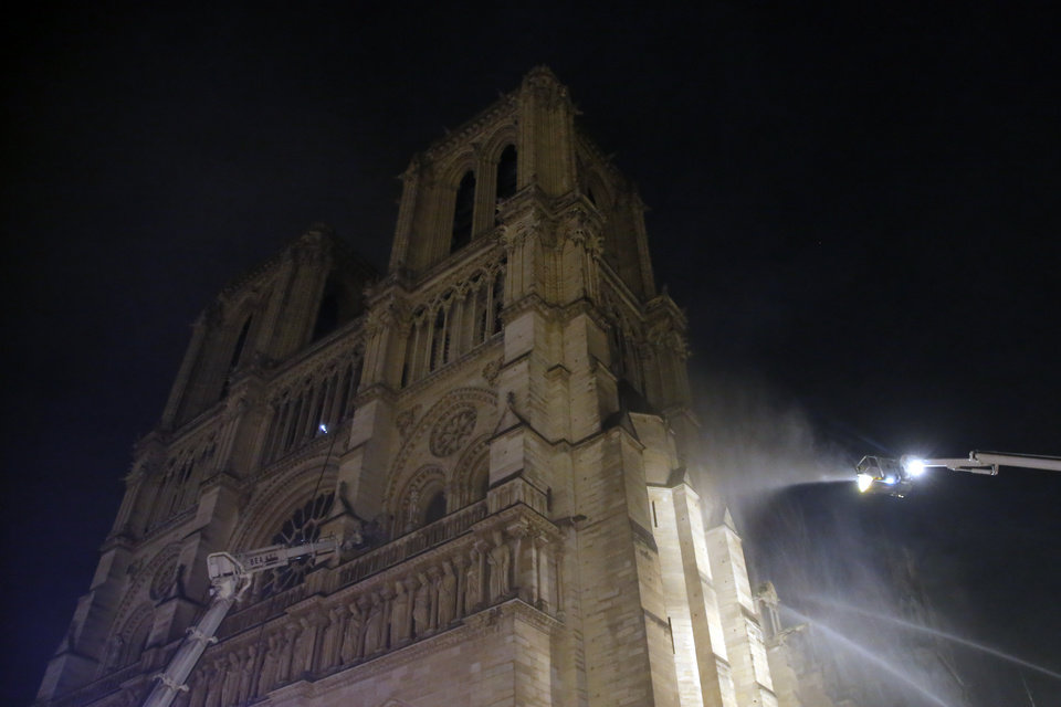 Photo - Fire fighter work at Notre Dame cathedral burning in Paris, Monday, April 15, 2019. A catastrophic fire engulfed the upper reaches of Paris' soaring Notre Dame Cathedral as it was undergoing renovations Monday, threatening one of the greatest architectural treasures of the Western world as tourists and Parisians looked on aghast from the streets below. (AP Photo/Michel Euler)