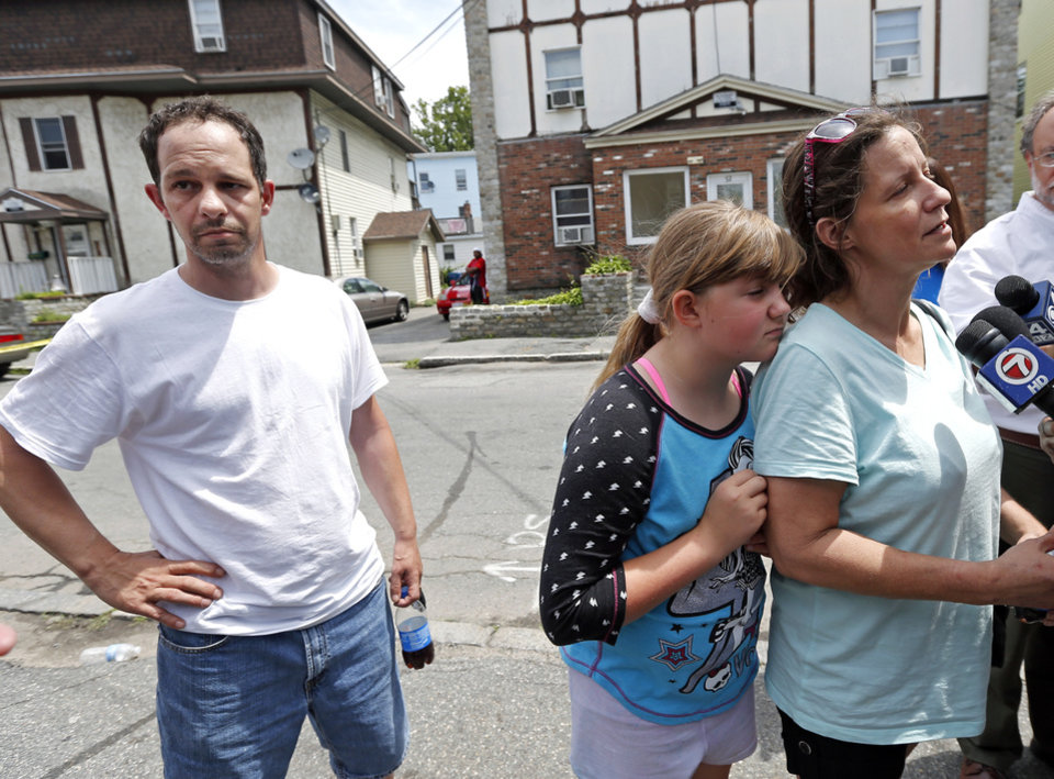 Photo - Geri Boyles, far right, with her daughter Corinna, 10, speaks to reporters as neighbor Randy Perry reacts, at left, outside a burned three-story apartment and business building in Lowell, Mass., Thursday, July 10, 2014. The three neighbors lost people they knew in the fast-moving pre-dawn fire where officials said seven people died. (AP Photo/Elise Amendola)