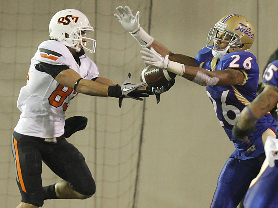 Photo - Tulsa's Dexter McCoil (26) breaks up a pass for Oklahoma State's Colton Chelf (83) during a college football game between the Oklahoma State University Cowboys and the University of Tulsa Golden Hurricane at H.A. Chapman Stadium in Tulsa, Okla., Sunday, Sept. 18, 2011. Photo by Chris Landsberger, The Oklahoman