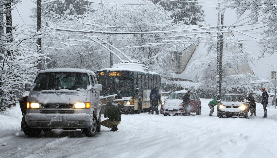 Photo - FILE - In this Jan. 15, 2013 file photo, cars and a bus sit stuck on a hill on 24th Avenue East during a snowstorm in Seattle. With 2013's winter half-over and mild weather holding for Seattle, the city could make it through the season without a significant snowfall. Meteorologist Johnny Burg said said Monday, Feb. 11, 2013, that Seattle typically goes without winter snow only once or twice a decade. (AP Photo/Ted S. Warren, File)