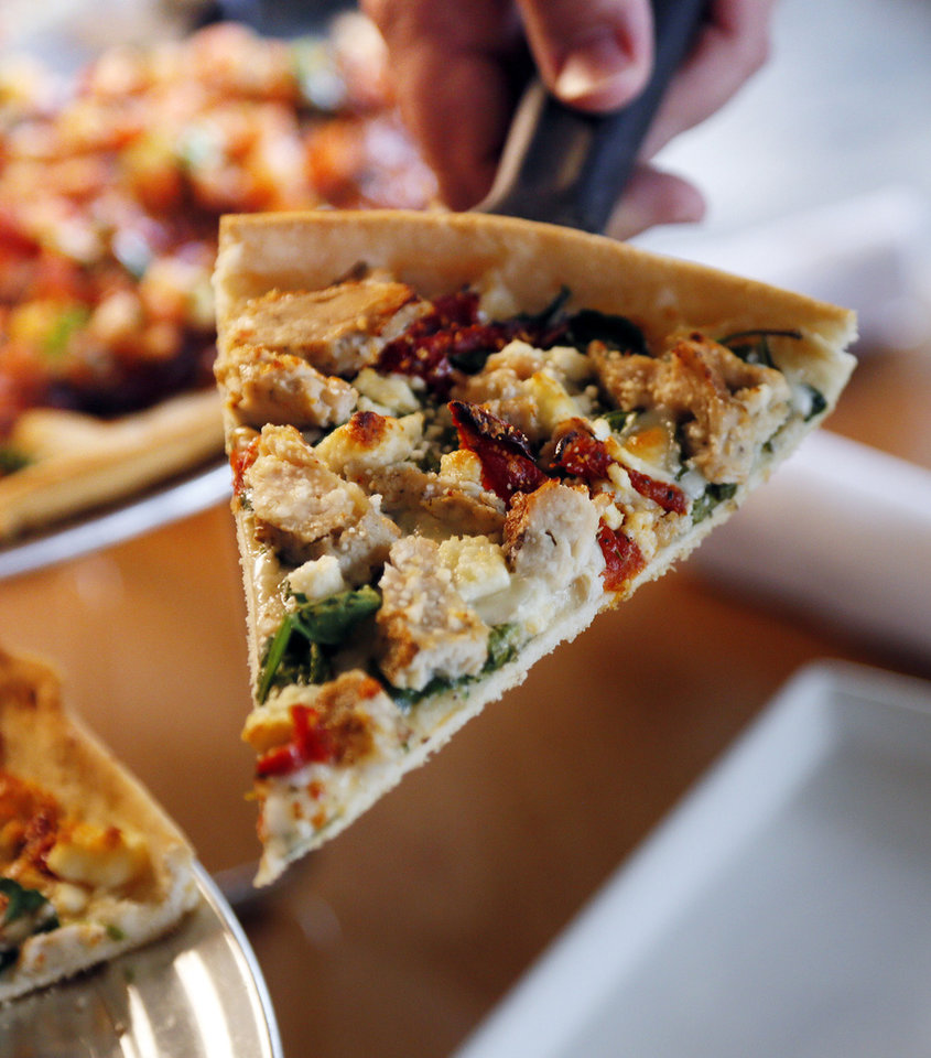 A slice of Mediterranean pizza at Pizza 23 is topped with grilled chicken, sun-dried tomatoes, Feta and spinach. <strong>NATE BILLINGS - NATE BILLINGS</strong>
