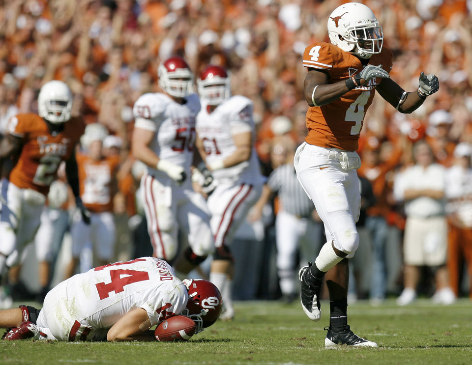 Photo - Aaron Williams of Texas celebrates in front of OU's Sam Bradford after sacking Bradford during the Red River Rivalry college football game between the University of Oklahoma Sooners (OU) and the University of Texas Longhorns (UT) at the Cotton Bowl in Dallas, Texas, Saturday, Oct. 17, 2009. Bradford left the game with an injury and did not return. Photo by Bryan Terry, The Oklahoman