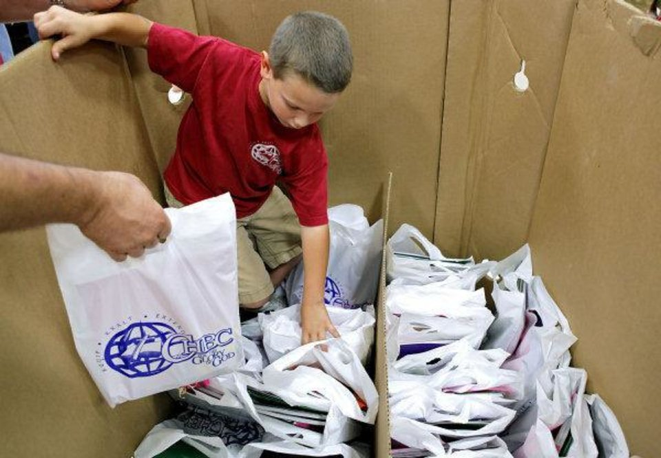 Photo - Brady Sampson, 7, and other members of Capitol Hill Baptist Church in south Oklahoma City, fill bags and boxes with school supplies to be distributed during the church's annual carnival and school supply give-away on Sunday.  JOHN CLANTON - John Clanton