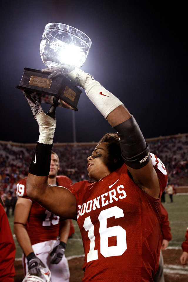 Photo - Lewis Baker hoists the Bedlam Trophy after the college football game between the University of Oklahoma Sooners (OU) and the Oklahoma State University Cowboys (OSU) at the Gaylord Family-Memorial Stadium on Saturday, Nov. 24, 2007, in Norman, Okla. 