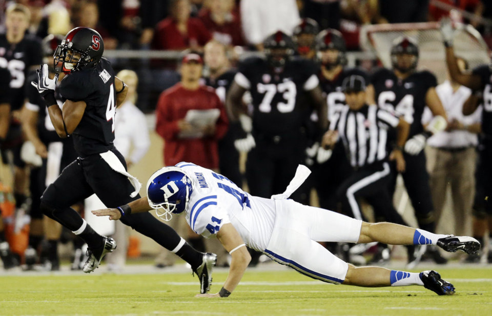 Photo -   Stanford's Drew Terrell, left, runs past Duke punter Will Monday on his way to a 76-yard punt return for a touchdown during the first half of an NCAA college football game in Stanford, Calif., Saturday, Sept. 8, 2012. (AP Photo/Marcio Jose Sanchez)
