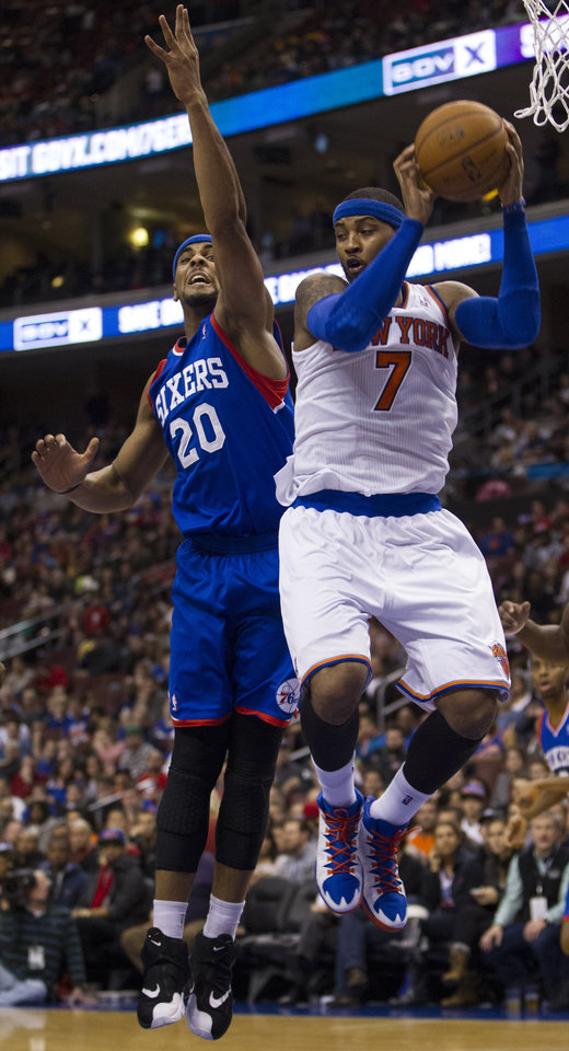 Photo - New York Knicks' Carmelo Anthony, right, pulls down the rebound over Philadelphia 76ers' Brandon Davies, left, during the first half of an NBA basketball game, Saturday, Jan. 11, 2014, in Philadelphia.  (AP Photo/Chris Szagola)