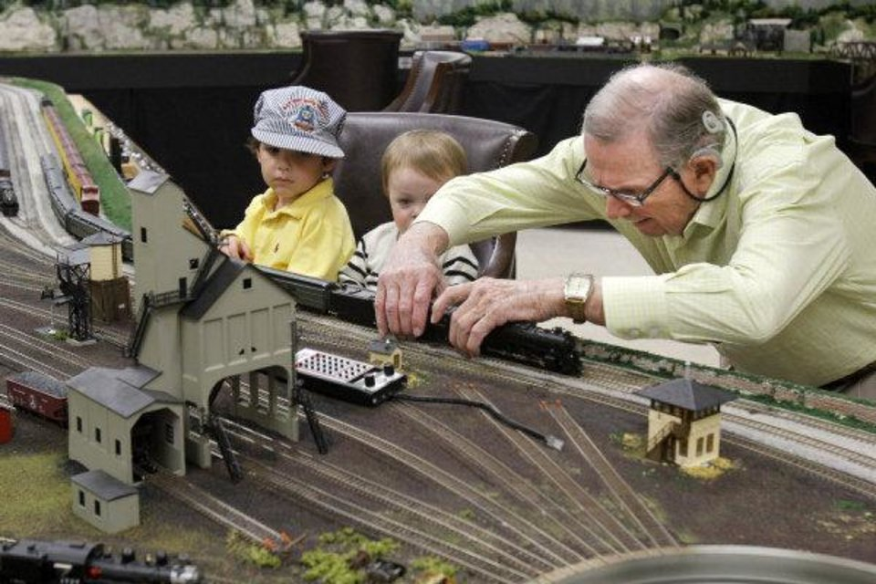 Photo - Jimmy Samis demonstrates his train collection to his great-grandchildren Sam Kirkpatrick, 3, and 16-month-old Thomas Fellers, at his home in Nichols Hills on Oct. 28. Photo by Paul Hellstern, The Oklahoman  PAUL HELLSTERN
