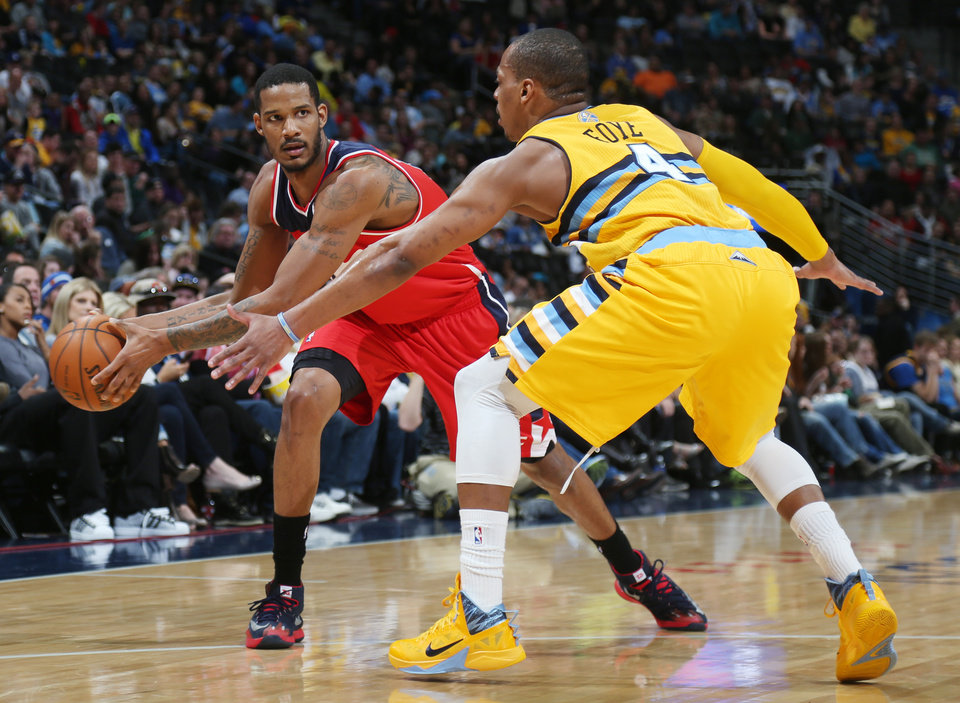 Photo - Washington Wizards forward Trevor Ariza, left, looks to pass ball inside as Denver Nuggets guard Randy Foye covers in the first quarter of an NBA basketball game in Denver on Sunday, March 23, 2014. (AP Photo/David Zalubowski)
