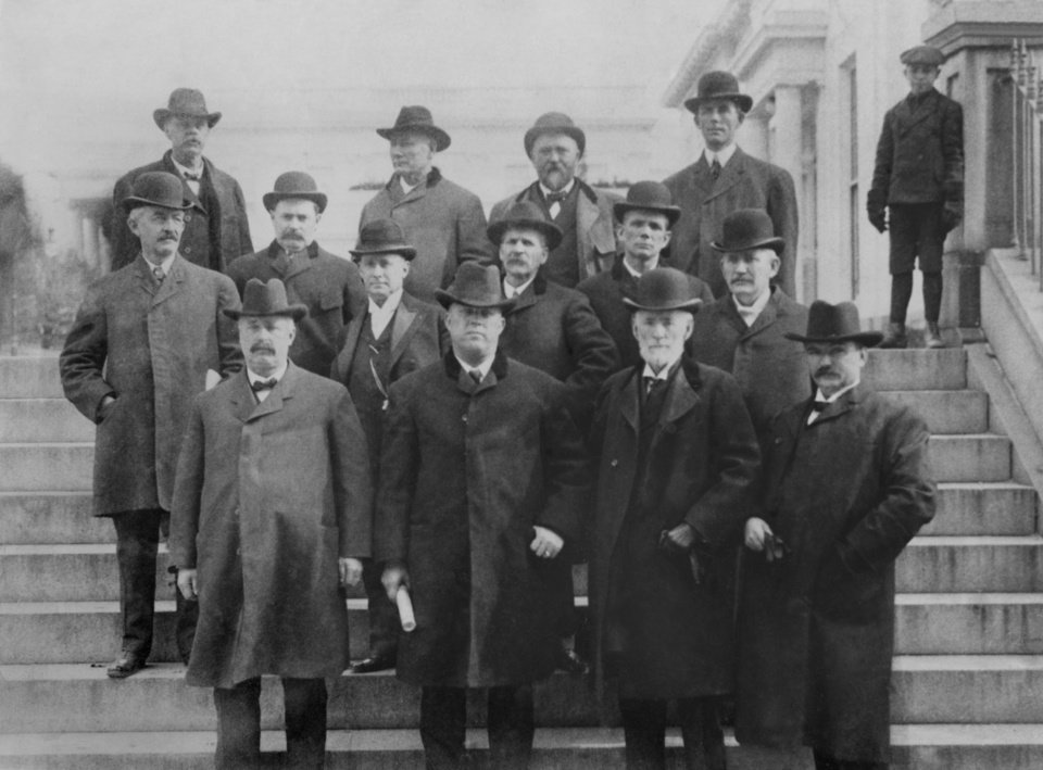 """A committee was appointed in 1905 to seek the aid of President Theodore Roosevelt in obtaining statehood for Oklahoma.  The committee members are, front, left to right, William Johnson, Charles G. Jones, Sen. Cullum and Judge Thomas Doyle;  second row, Professor David L. Boyd, Fred Parkingson, Charles Hunter, William Anderson, Grant Victor and William S. McCaull;  back row, Robert Lowery, Alf Hammer, Sen. Merrian and Mr. Greer.  The boy is Quentin Roosevelt, son of the president."""