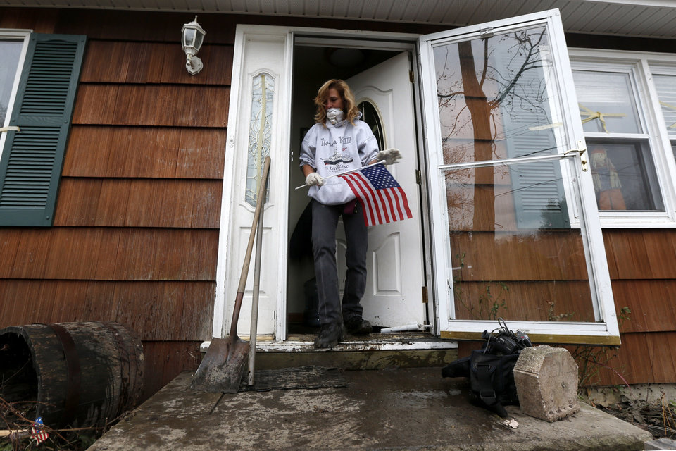Kathleen Seemar removes a U.S. flag from her home, which was flooded during superstorm Sandy, as she started the cleanup process, Thursday, Nov. 1, 2012, in Brick, N.J. Three days after Sandy slammed the mid-Atlantic and the Northeast, New York and New Jersey struggled to get back on their feet, the U.S. death toll climbed to more than 80, and more than 4.6 million homes and businesses were still without power. (AP Photo/Julio Cortez) ORG XMIT: NJJC113