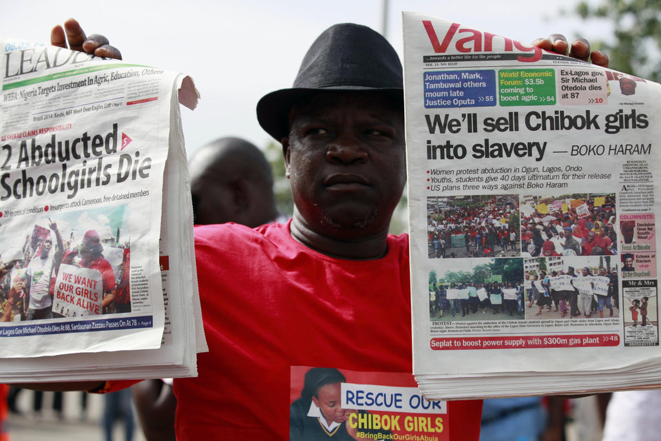 Photo - A man display copies of local newspapers during a demonstration calling on the government to rescue kidnapped school girls from Chibok government secondary school, outside the defense  headquarters, in Abuja, Nigeria, Tuesday, May 6, 2014.  The plight — and the failure of the Nigerian military to find them — has drawn international attention to an escalating Islamic extremist insurrection that has killed more than 1,500 so far this year. Boko Haram, the name means