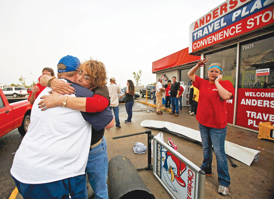 Staci Harris, left, hugs fellow employee Stacey Hendley outside the Anderson Travel Plaza after a tornado damaged the area near Interstate 240 and Choctaw Road on Monday in Oklahoma City. Photo by Chris Landsberger,  The Oklahoman