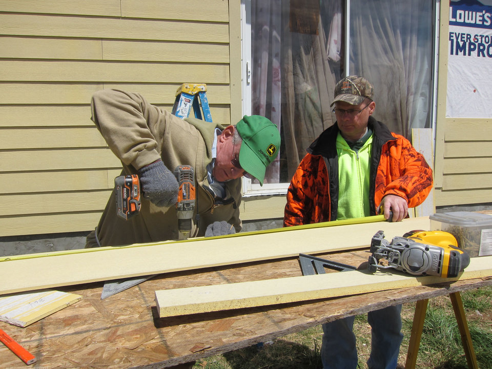 Photo - Bruce Nivens of Alvord, Texas, works with Darryl Epperson of Florence, Ky, to drill siding that will be attached to a Newalla home as part of NOMADS home repair project.  Photo by Carla Hinton, The Oklahoman