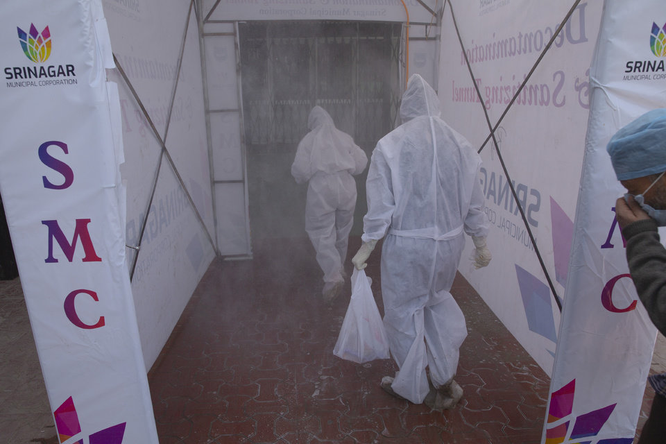 Photo -  Medical staff wearing protective gear walk inside a disinfecting tunnel outside a hospital where most VOVID-19 patients are being treated in Srinagar, Indian controlled Kashmir, Friday, April 3, 2020. The new coronavirus causes mild or moderate symptoms for most people, but for some, especially older adults and people with existing health problems, it can cause more severe illness or death. (AP Photo/ Dar Yasin)