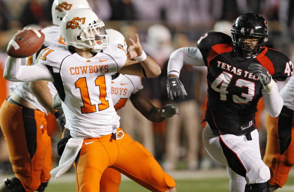 Photo - Oklahoma State's Zac Robinson (11) looks to throw the ball under the pressure of Texas Tech's McKinner Dixon (43) during the second half of the college football game between the Oklahoma State University Cowboys (OSU) and the Texas Tech Red Raiders at Jones AT&T Stadium on Saturday, Nov. 8, 2008, in Lubbock, Tex.BY CHRIS LANDSBERGER/THE OKLAHOMAN
