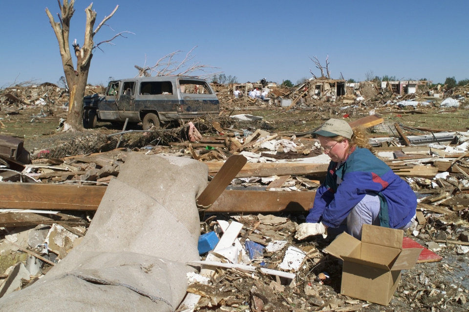 Wendy Nix helps with tornado damage cleanup on Lamar street in Del City.