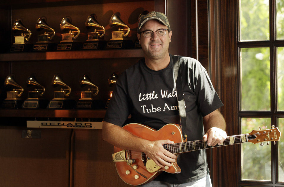 In this Aug. 16, 2011 photo, Vince Gill is shown with some of his Grammy awards at his home in Nashville, Tenn. (AP Photo/Mark Humphrey) ORG XMIT: TNMH202
