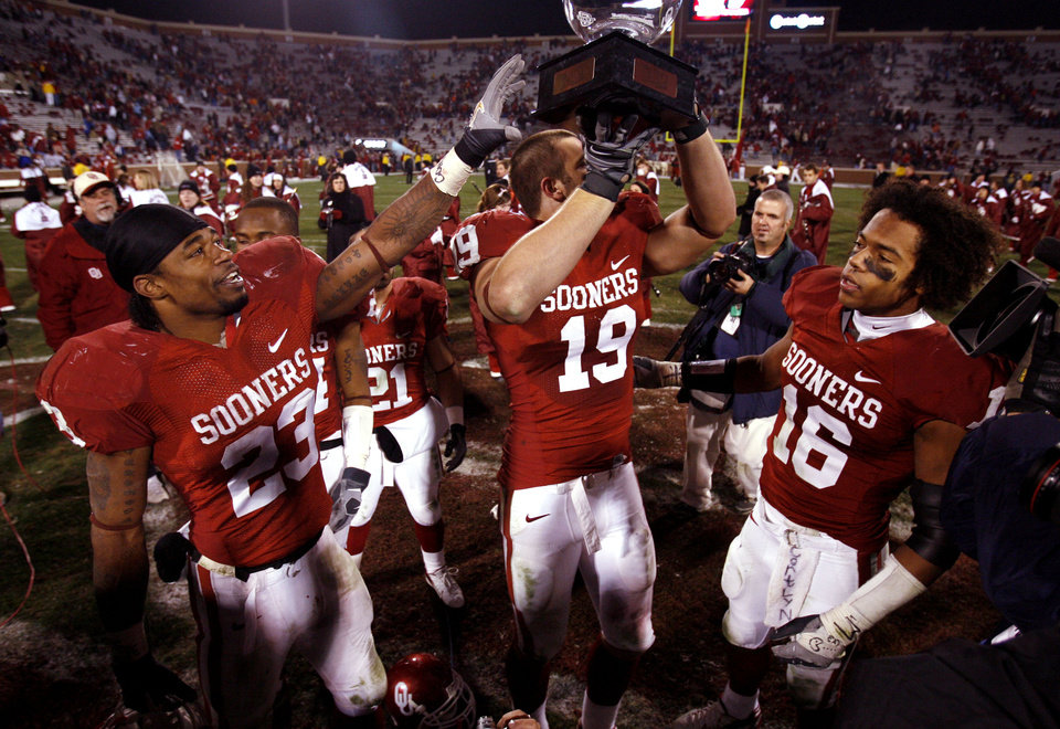 Photo - Allen Patrick (23) reaches for the Bedlam Trophy held by Joe Jon Finley (19)during the second half of the college football game between the University of Oklahoma Sooners (OU) and the Oklahoma State University Cowboys (OSU) at the Gaylord Family-Memorial Stadium on Saturday, Nov. 24, 2007, in Norman, Okla.  At right is Lewis Baker (16).