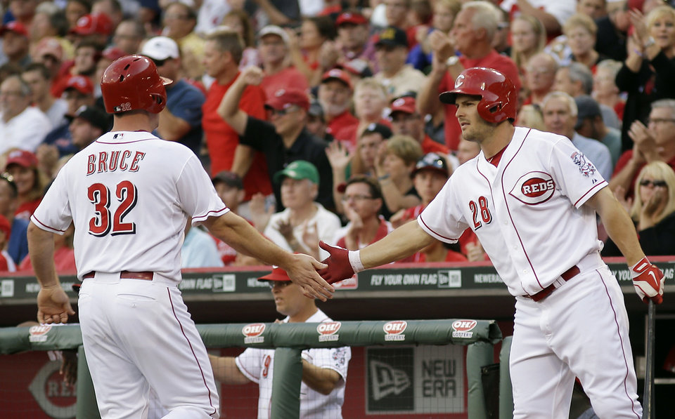 Photo - Jay Bruce (32) is congratulated by Chris Heisey, right, after scoring on a base hit by Devin Mesoraco off of Boston Red Sox pitcher Joe Kelly in the first inning of a baseball game, Tuesday, Aug. 12, 2014, in Cincinnati. (AP Photo/Tony Tribble)
