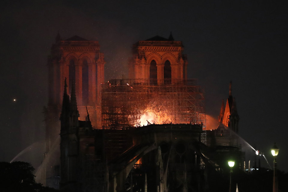 Photo - Fire fighters try to extinguish the fire as Notre Dame cathedral is burning in Paris, Monday, April 15, 2019. A catastrophic fire engulfed the upper reaches of Paris' soaring Notre Dame Cathedral as it was undergoing renovations Monday, threatening one of the greatest architectural treasures of the Western world as tourists and Parisians looked on aghast from the streets below. (AP Photo/Christophe Ena)