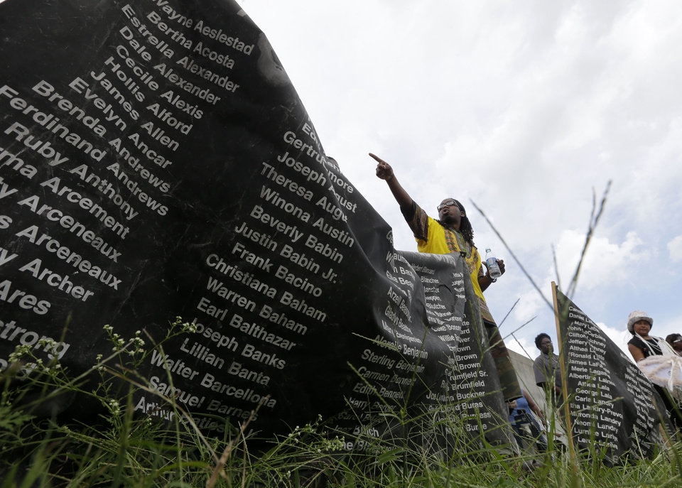 Photo - Dr. Samori Camara speaks at a remembrance event along the Industrial Canal flood wall, seen in background, in the Lower 9th Ward section of New Orleans, on the ninth Anniversary of Hurricane Katrina, Friday, Aug. 29, 2014. (AP Photo/Gerald Herbert)
