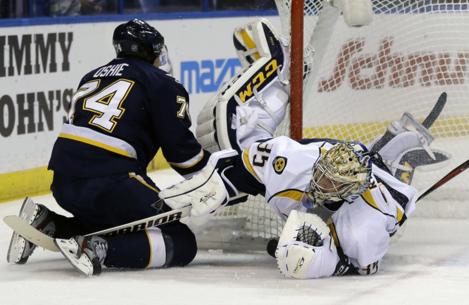 Nashville Predators goalie Pekka Rinne, right, of Finland, falls to the ice after colliding with St. Louis Blues\' T.J. Oshie, left, during the second period of an NHL hockey game on Thursday, Jan. 24, 2013, in St. Louis. (AP Photo/Jeff Roberson)