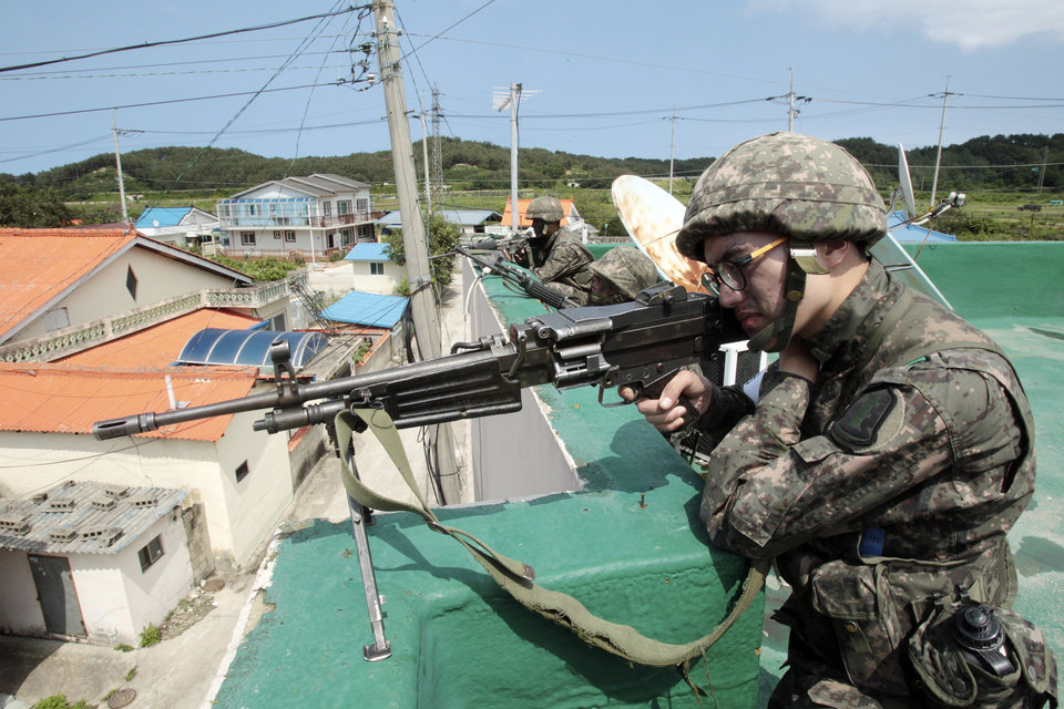 Photo - South Korean army soldiers aim their machine guns as they search for a South Korean conscript soldier who is on the run after a shooting incident in Goseong, South Korea, Sunday, June 22, 2014. South Korean military authorities have surrounded a soldier who fled his border outpost after killing five comrades the day before and were trying to persuade him to surrender, a defense official said Sunday.(AP Photo/Ahn Young-joon)