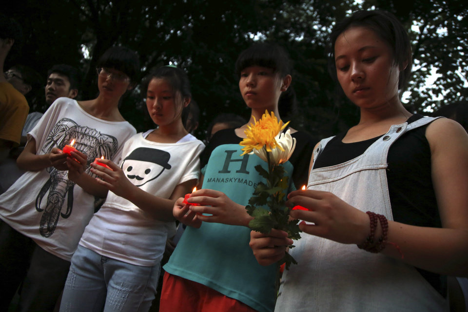 Photo - Residents gather to mourn for the two victims of the Asiana airline plane crash in San Francisco at a park in Jiangshan city in eastern China's Zhejiang province on Monday, July 8 2013. Chinese state media and Asiana Airlines have identified the two victims of the Asiana Airlines crash at San Francisco International Airport girls as Ye Mengyuan and Wang Linjia, students in Zhejiang, an affluent coastal province in eastern China.  (AP Photo) CHINA OUT
