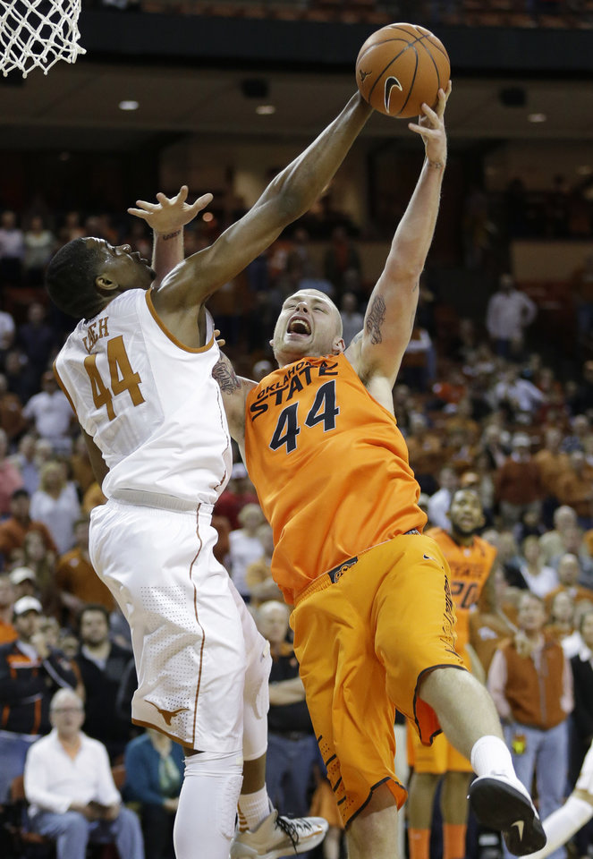 Texas\' Prince Ibeh, left, and Oklahoma State\'s Philip Jurick, right, reach for a rebound during the first half of an NCAA college basketball game, Saturday, Feb. 9, 2013, in Austin, Texas. (AP Photo/Eric Gay) ORG XMIT: TXEG101