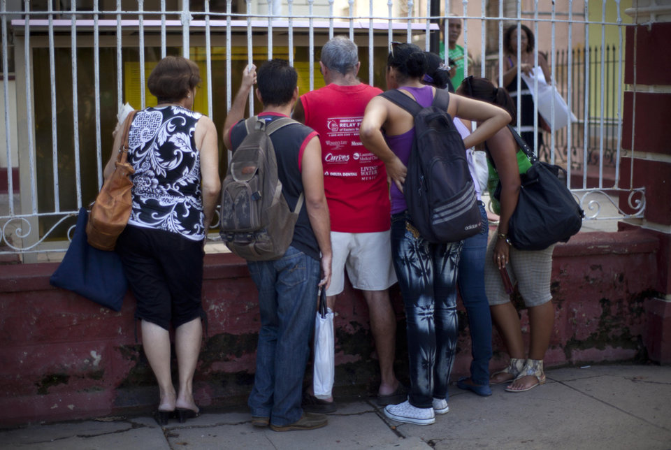Photo -   People read adjustments to the migratory policy, posted on a wrought iron fence of an immigration office in Havana, Cuba, Tuesday, Oct 16, 2012. The Cuban government announced Tuesday that it will no longer require islanders to apply for an exit visa, eliminating a much-loathed bureaucratic procedure that has been a major impediment for many seeking to travel overseas for more than a half-century. (AP Photo/Ramon Espinosa)