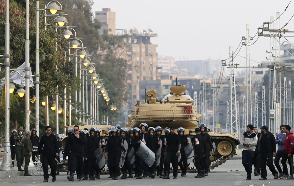 """Photo - Egyptian riot police walk past a military tank guarding the presidential palace in Cairo, Egypt, Sunday, Dec. 16, 2012. Key Egyptian rights groups called Sunday for a repeat of the first round of the constitutional referendum, alleging the vote was marred by widespread violations. Islamists who back the disputed charter claimed they were in the lead with a majority of """"yes"""" votes. (AP Photo/Hassan Ammar)"""