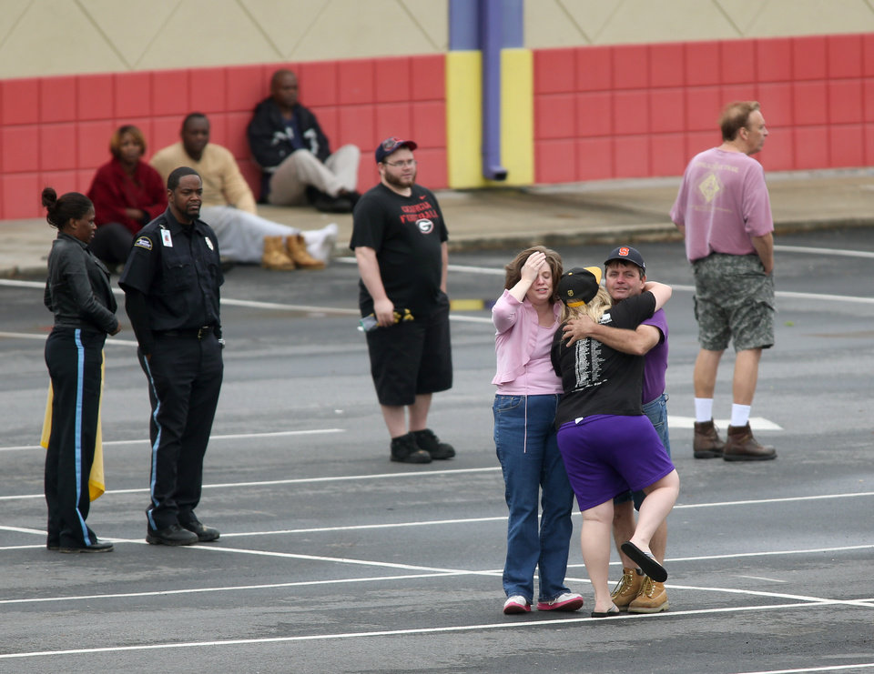 Photo - A FedEx employee, facing, is consoled by family or friends as other FedEx employees wait to meet their family at a near by business after they were evacuated from the Airport Road FedEx facility after an early morning shooting Tuesday April 29, 2014, in Kennesaw, Ga. A shooter opened fire at a FedEx center wounding at least six people before police swarmed the facility. The shooter was found dead from an apparent self-inflicted gunshot wound. (AP Photo/Jason Getz)