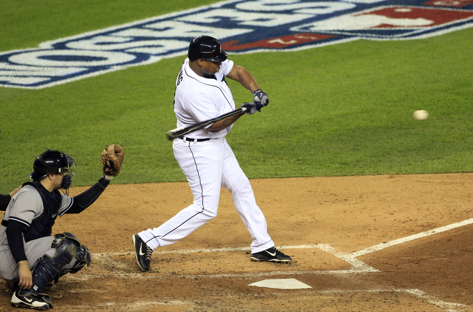 Photo -   Detroit Tigers' Delmon Young hits a home run in the fourth inning during Game 3 of the American League championship series against the New York Yankees Tuesday, Oct. 16, 2012, in Detroit. New York Yankees catcher Russell Martin is at left. (AP Photo/Carlos Osorio)