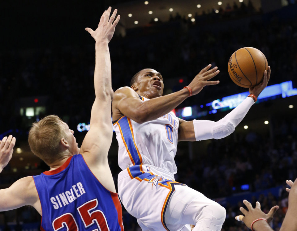 Photo - Oklahoma City Thunder guard Russell Westbrook (0) shoots in front of Detroit Pistons guard Kyle Singler (25) during the fourth quarter of an NBA basketball game in Oklahoma City, Wednesday, April 16, 2014. Oklahoma City won 112-111. (AP Photo/Sue Ogrocki)