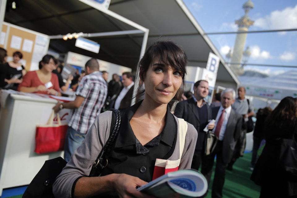 "Estelle Borrell, 24, visits a job fair in Paris, Thursday, Oct. 4, 2012. Estelle Borrell knew she wanted to work in law since she was a teenager, when she interned at a court in Versailles, France. ""The lawyers in their black robes, they were like gods to me,"" said the 24-year-old Parisian.  Borrell studied law at Vienna University, where she dreamed of putting her passion into practice at an international organization. She got a shock when she began working at a Vienna law firm.  (AP Photo/Christophe Ena)"