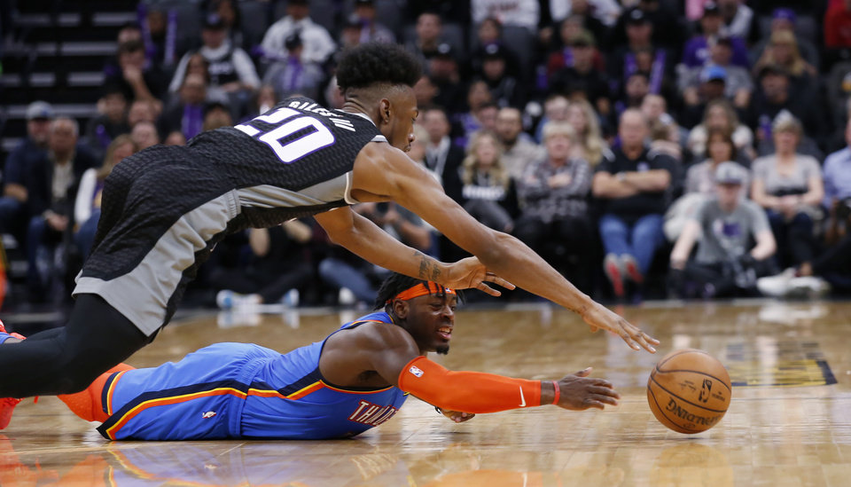 Photo - Sacramento Kings forward Harry Giles III, top, and Oklahoma City Thunder guard Luguentz Dort, right, reach for the ball during the second half of an NBA basketball game in Sacramento, Calif., Wednesday, Jan. 29, 2020. The Thunder won 120-100. (AP Photo/Rich Pedroncelli)