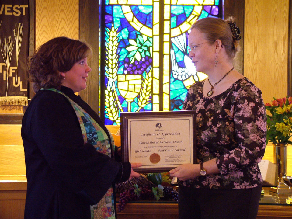 Julie Murray, right, Girl Scout Troop Leader and Service Unit Director, Red Lands Council, presents Rev. Glenda Skinner-Noble, Pastor of Harrah United Methodist Church, with a appreciation plaque on Nov. 12. The Girls Scouts thanked the church membership for its providing a place for meetings and support. Murray said that for one special meeting in December there will be 150 Scouts creating Christmas ornaments in the church's Fellowship Hall.<br/><b>Community Photo By:</b> Lin Archer<br/><b>Submitted By:</b> Lin, Harrah
