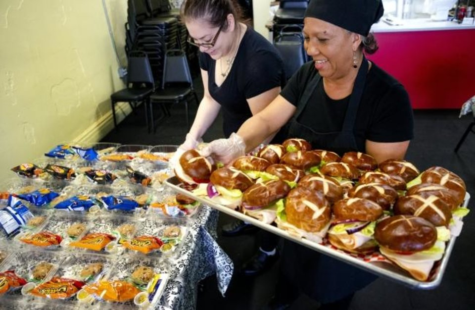 Photo -  Donna Heins and Tiara Markcum, left, prepare part of the 200 lunches that Clara Belle's restaurant is catering for the staff at Mabel Bassett in McLoud, Okla. on Friday, April 3, 2020. Prison volunteers raised money to pay for lunch boxes for staff at the prison.  [Chris Landsberger/The Oklahoman]