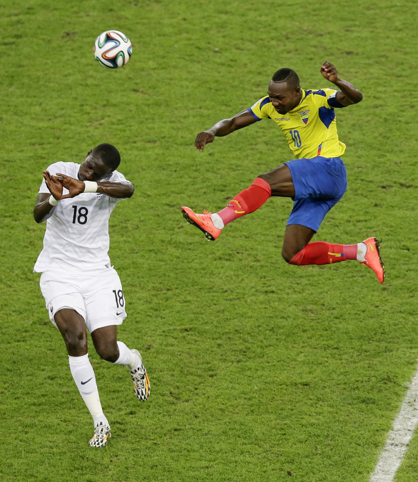 Photo - France's Moussa Sissoko and Ecuador's Walter Ayovi, right, battle for a ball during the group E World Cup soccer match between Ecuador and France at the Maracana Stadium in Rio de Janeiro, Brazil, Wednesday, June 25, 2014. (AP Photo/Andrew Medichini)