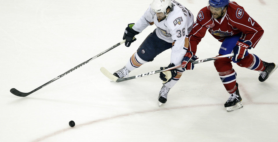 Photo - Oklahoma City's Hunter Tremblay fights for control of a puck with Hamilton's Ian Schultz during the AHL hockey game between the Oklahoma City Barons and the Hamilton Bulldogs at the Cox Convention Center in Oklahoma City, Tuesday, April 3, 2012. Photo by Sarah Phipps, The Oklahoman