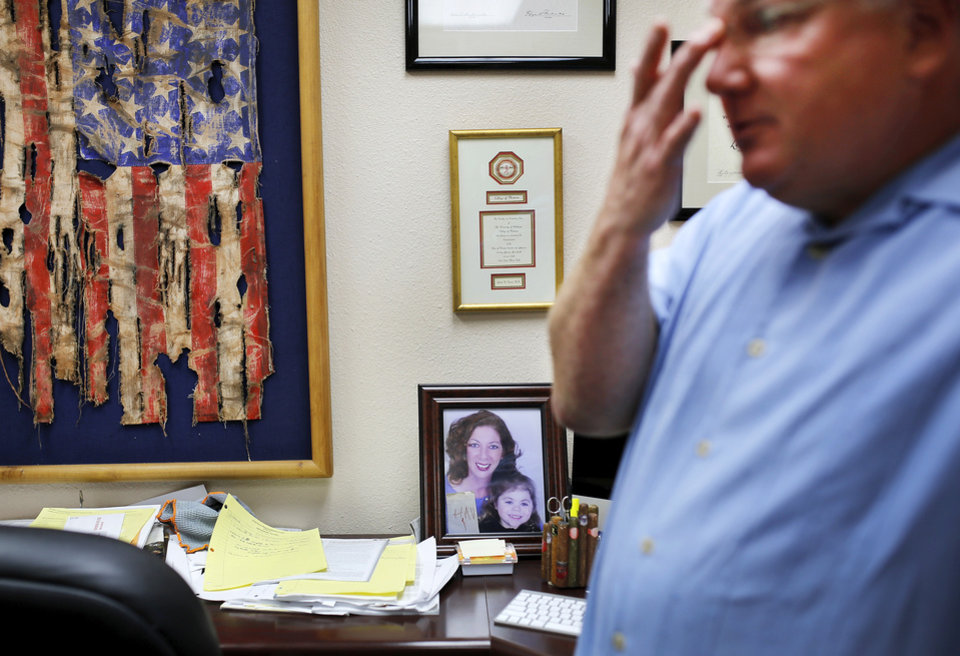 Photo - Dr.  Leland Dennis, a psychiatrist in Elk City, is retiring this month.    He is shown in his office on Tuesday, April 29, 2014.  Photo on his desk shows his wife and their daughter, who died at age 11. Photo by Jim Beckel, The Oklahoman