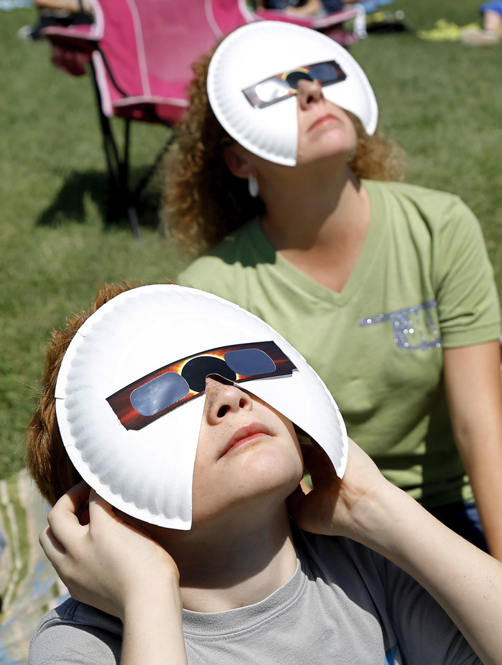 Photo - Willy Brandt. front, and teacher asistant Tassie Burke wear modified viewing glasses to watch the eclipse. The entire student body, faculty and some parents gathered in a field on the north side of  James Griffith Intermediate School to view the solar eclipse Monday afternoon, Aug. 21, 2017.  Special glasses with very dark lenses were purchased to allow teachers and students to safely view the celestial event. Children were served  Moon Pies as a snack to enjoy while viewing the eclipse. Photo by Jim Beckel, The Oklahoman