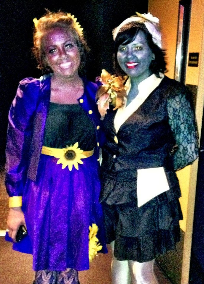 Photo - Two fans dressed in the gaudy makeup and fashions of the movie's Capitol citizens to attend a midnight screening of