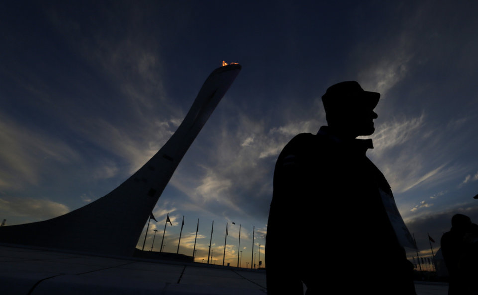 Photo - A security team member keeps watch near the Olympic Cauldron as the sun sets at the 2014 Winter Olympics, Friday, Feb. 14, 2014, in Sochi, Russia. (AP Photo/David J. Phillip )