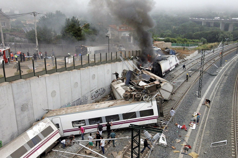 Photo - In this photo taken on Wednesday July 24 2013, Emergency personnel respond to the scene of a train derailment in Santiago de Compostela, Spain. Police say they have detained the driver of a train that crashed in northwestern Spain and killed 78 people. Galicia region National Police Chief Jaime Iglesias says driver Francisco Jose Garzon Amo was officially detained in the hospital where is recovering. (AP Photo/La Voz de Galicia/Monica Ferreiros)