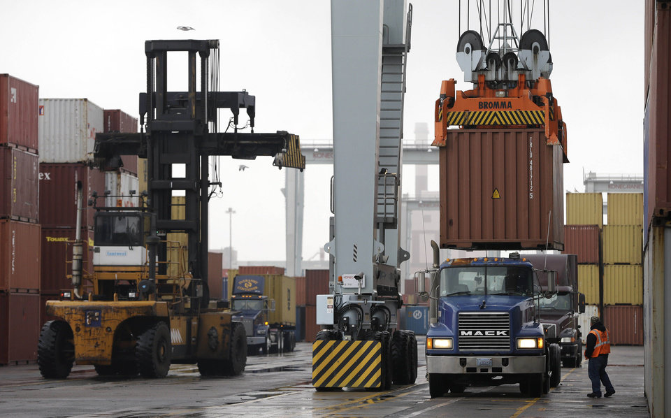FILE - In this Dec. 18, 2012 file photo, a truck driver watches as a freight container, right, is lowered onto a tractor trailer by a container crane at the Port of Boston in Boston. The crane and a reach stacker, left, are operated by longshoremen at the port. The longshoremen\'s union may strike if they are unable to reach an agreement on their contract, which expires Dec. 29, 2012. A walkout by dock workers represented by the International Longshoremen's Association would bring commerce to a near halt at ports from Boston to Houston. (AP Photo/Steven Senne, File)