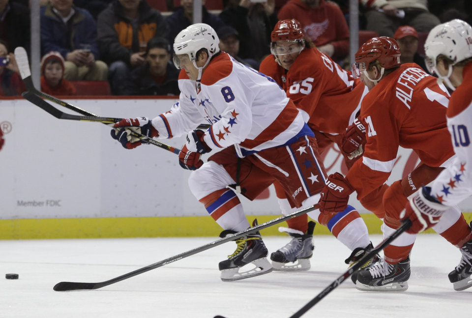 Photo - Washington Capitals right wing Alex Ovechkin (8) breaks away from Detroit Red Wings defenseman Danny DeKeyser (65) and right wing Daniel Alfredsson (11) of Sweden during the first period of an NHL hockey game in Detroit, Friday, Jan. 31, 2014. (AP Photo/Carlos Osorio)