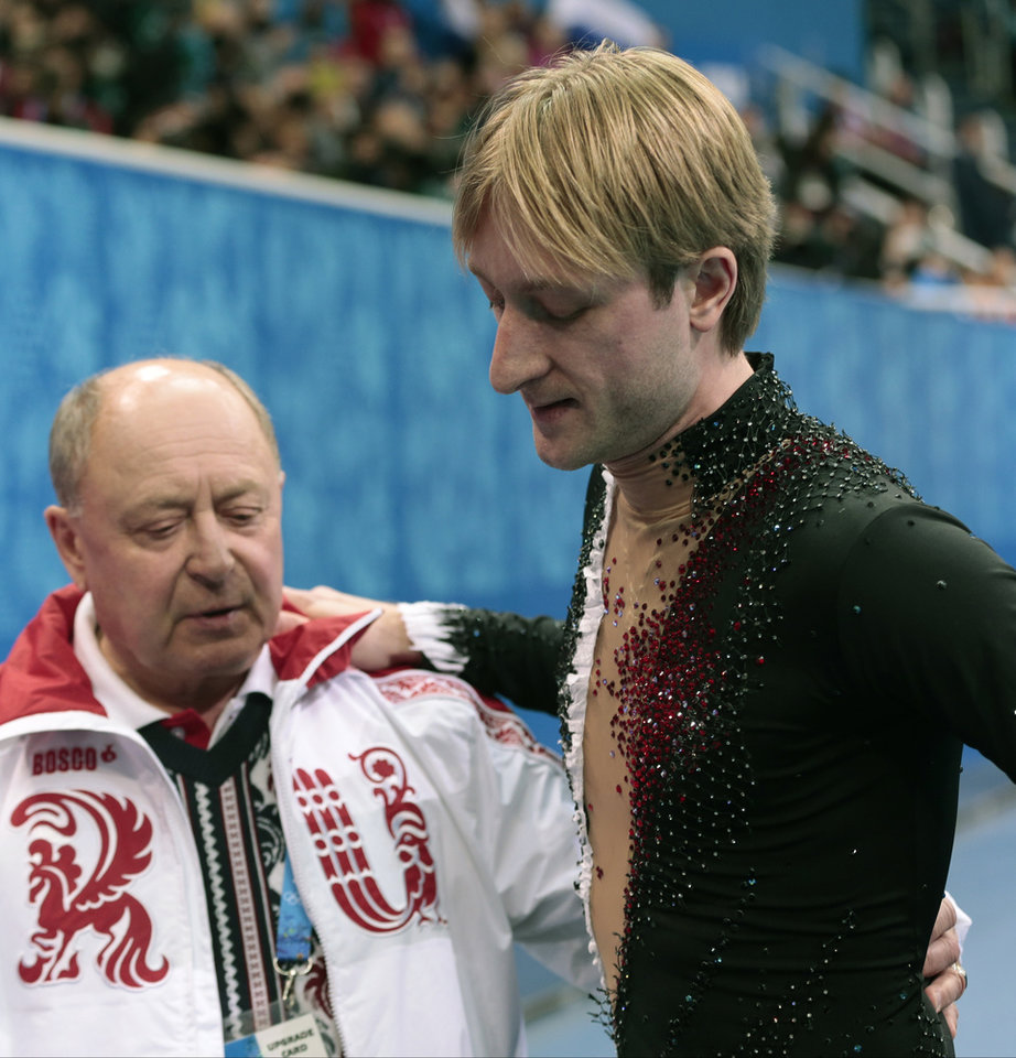 Photo - Evgeni Plushenko of Russia, right, and his coach Alexei Mishin leave after Plushenko pulled out of the men's short program figure skating competition due to illness at the Iceberg Skating Palace during the 2014 Winter Olympics, Thursday, Feb. 13, 2014, in Sochi, Russia. (AP Photo/Ivan Sekretarev)