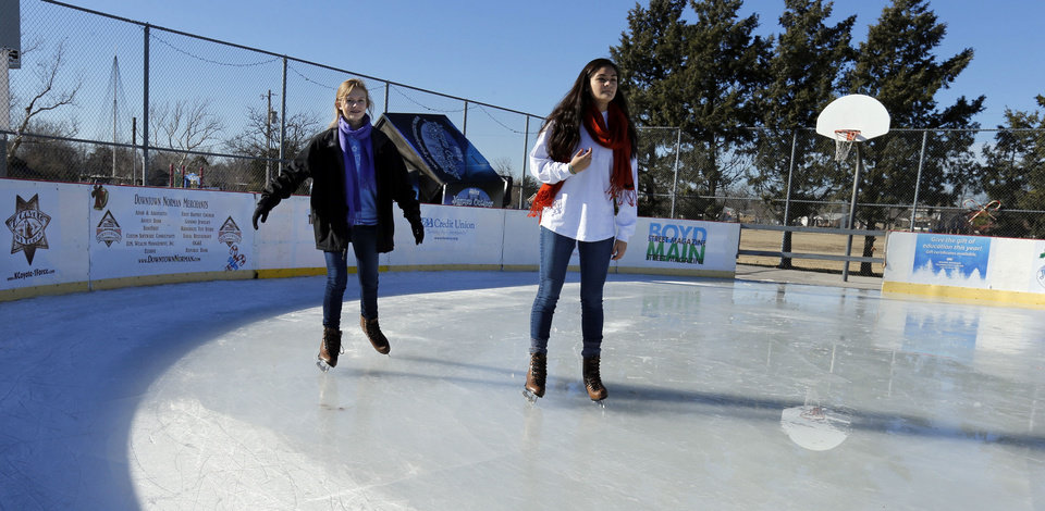 Photo - Kelsey Floyd, left, of Norman,  and friend Sophie Lopez, of Washington, D.C., both 15, try out the ice at the outdoor rink in Andrews Park in Norman. PHOTO BY STEVE SISNEY, THE OKLAHOMAN  STEVE SISNEY